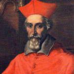 Bearded man wearing red, long clothing.
